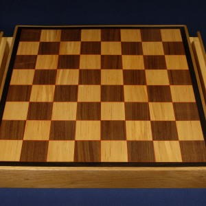 Another chess board of birch and walnut with red veneer highlights and ebony trim. Includes drawers.