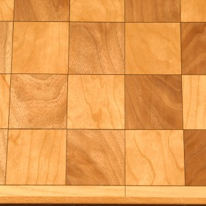 Chess board with walnut and cherry and a black veneer highlight which is accented by an ash trim.