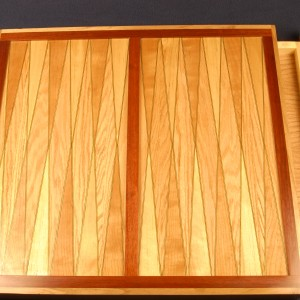 Oreo design. Two darker veneers with a lighter one in between. This backgammon board is of cherry, birch and red oak.